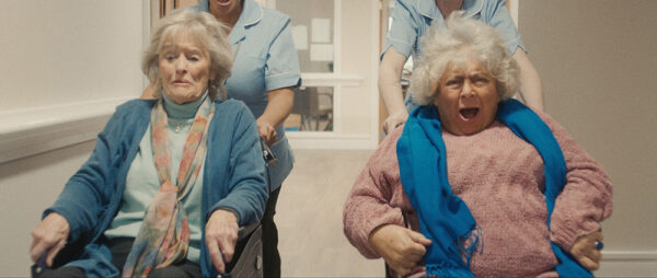 Audrey (Miriam Margolyes) and Dora (Virgina McKenna) are being pushed a speed in wheelchairs along a care home corridor. From the short film Wings.